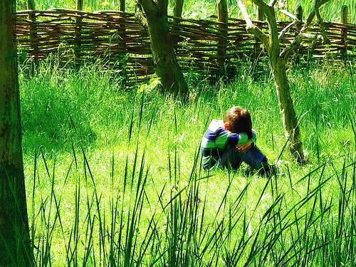フリー画像| 人物写真| 子供ポートレイト| 少年/男の子| 外国の子供| 落胆/落ち込む| 拗ねる| 草原の風景| 緑色/グリーン|