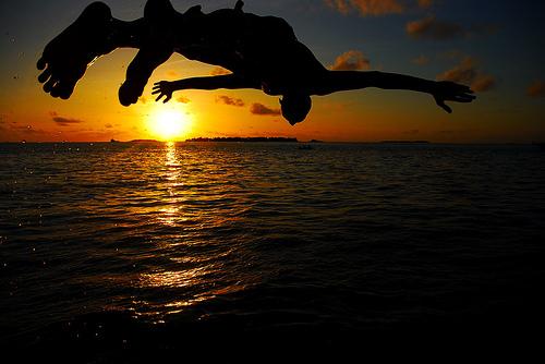 フリー画像|人物写真|一般ポートレイト|跳ぶ/ジャンプ|夕日/夕焼け/夕暮れ|海の風景|橙色/オレンジ|シルエット|